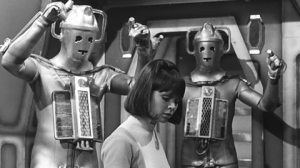 Zoe is hard at work as some Cybermen dance behind her...okay, that's really their menacing pose.